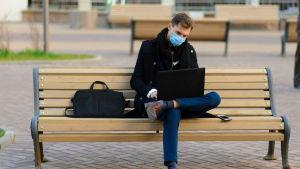 Man sitter på bänk och skriver på sin laptop.