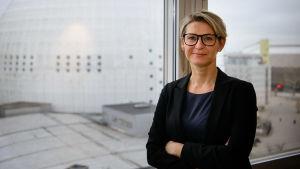 Jenny Silfverstrand på sitt kontor, i bakgrunden utsikt mot Globen i Stockholm.