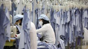 Bild på kvinnor som syr kläder i en klädfabrik. De bär munskydd och omges av blå tygbitar som hänger i ställningar ovanför dem.
