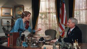 Märta står vid ett stort skrivbord och pekar bestämt mot presidenten som sitter i stolen.