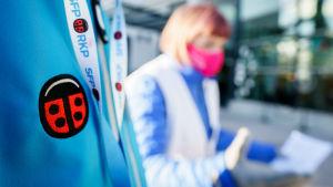 RKP.n vaalitapahtuma. Etualalla henkilö jonka pusakassa RKP:n leppäkerttu-logo ja kaulassa nauha, jossa teksti SFP-RKP, taustalla nainen jakamassa vaaliesitettä.