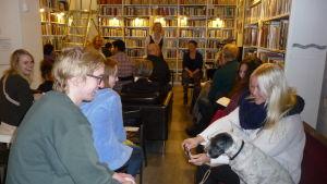Publik i en bokhandel. De sitter och väntar på att en föreställning ska börja. En hund väcker publikens förtjusning.