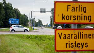 En vit bil står i en korsning. I förgrunden syns ett trafikmärke där det står farlig korsning.