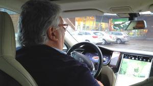 Immo Toivari sitter inne i sin elbil och kör
