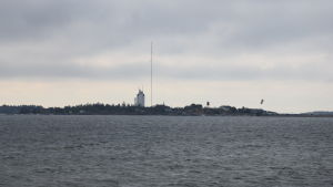 Udde med ett torn och en mast, en kitesurfare i förgrunden.