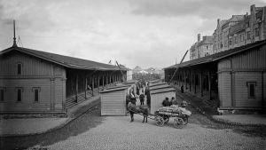 Häst, kärra och låga träbyggnader - Helsingfors 1909