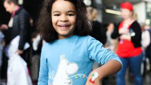 Ett leende barn visar fejk-tatuering