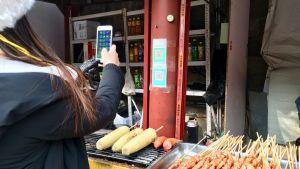 kiinalainen nainen maksaa mobiilisti katukeittiössä