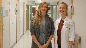 Två kvinnor i en hälsocentralskorridor.