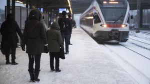 Tåg anländer till perrong, människor står och väntar
