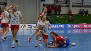 EN HIFK-spelare har bollen och en BK-spelare ligger på golvet.
