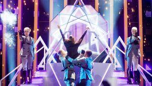 kvinna kastar sig ner från scenen i armarna på sina dansare