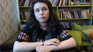 Alina Petrovitj är något så ovanligt som en rysk feminist. Här sitter hon med armarna i kors i en grön soffa framför en bokhylla.