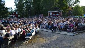 Publik sitter på läktare utomhus. Det är fullsatt och det ryms ungefär 1000 personer där. I bakgrunden syns hus och träd.