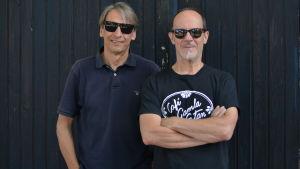 Två män i svarta/mörka skjortor och solglasögon. De står ute mot en svart trädörr/trävägg.