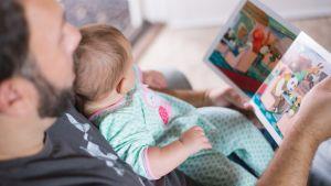 Pappa och bebis läser bok