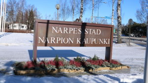 En skylt med texten Närpes stad står i en blomrabatt. Marken är täckt av snö.