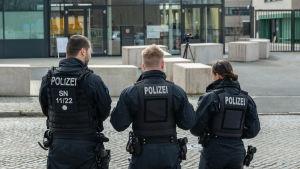 Tre tyska poliser i uniform står med ryggen emot.