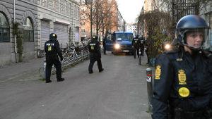 En handfull danska poliser i hjälm går mot en polisbil på en gata.