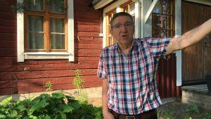 Henrik Wolff står framför Stockhuset i Mattby och förklarar om de nya planerna för Focus Mattliden i solskenet