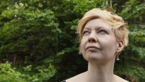 Kirjailija Marianna Kurtto saa tallustaa paljain jaloin taiteilijaresidenssin nurmella.