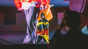 Räppäri Asap Rocky Blockfest-lavalla. Päällä räppärillä on keltamustapunainen liekkipaita, taustalla näkyy hänen kuvansa suurena screenillä.