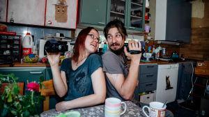 Hippihenkinen pariskunta istuu sotkuisessa ja värikkäässä keittiössä selät vastakkain videokamerat kädessä.
