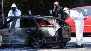Polisen inspekterar en bil som sattes i brand i närheten av platsen där dödsskjutningen ägde rum på måndag.