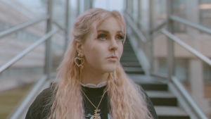 Vaaleanpunahiuksinen Ellinoora katsoo kohtalokkaasti sivulle lasisen portaikon edessä. Kuva rajattu rinnasta alaspäin. Päällä hänellä on musta paita, jonka kauluksesta tulee valkoinen röyhelö.