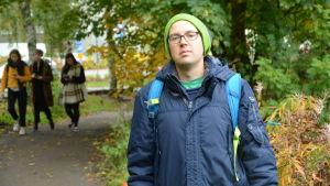 en kille i mörkblå jacka står vid en grönskande stig i ett parkområde i åbo