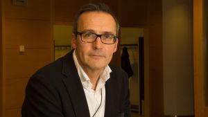 Porträttbild av Mikko Kautto iklädd kavaj, vitskjorta och glasögon.