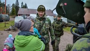 Dagisbarn och soldater framför ett militärfordon.