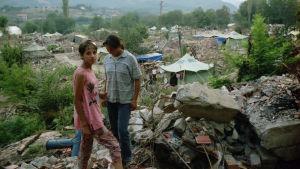 Två personer står på kulle med massor bråte och ruiner omkring sig.