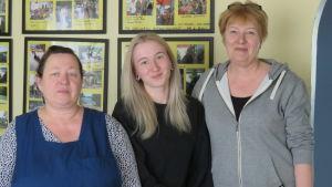 Tre kvinnor står framför en gul vägg med många fotografier.