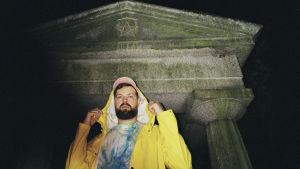 På bilden syns författaren Johannes Ekholm iklädd en gul regnjacka, färggrann t-skjorta och keps. Ekholm står framför en gammal byggnad.