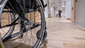 Ett rullstolshjul i förgrunden, i bakgrunden en lång korridor.