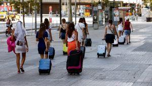 Flera personer drar på resväskor medan de går framåt på gata.