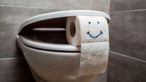 En toalettstol där locket är på glänt med hjälp av en toarulle som har ett leende på sig.