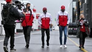 Kimi Räikkönen går bredvid varandra med mediafolk.