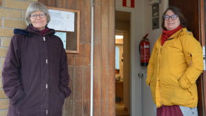 Två kvinnor vid en dörröppning.