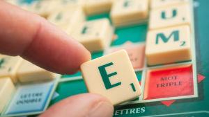En hand håller upp bokstaven E på ett Scrabble-bräde.