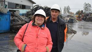 En kvinna och en man står på en industrigård, i bakgrunden skrot. Personerna är Harriet och Nils Rosenqvist.