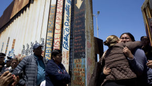 Två kvinnor kramar varandra vid grinden i gränsstaketet, andra mexikaner väntar på att få möta sina familjemedlemmar som bor i USA.