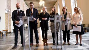 Touko Aalto (Gröna), Antti Lindtman (SDP), Laura Huhtasaari (Sannf), Li Andersson (VF), Anna-Maja Henriksson (SFP) och Päivi Räsänen (KD) står på rad i rikssalen.