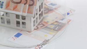 En temabild av ett miniatyrhus vars tak är gjort av femtioeuros sedlar. Över huset ligger en glaskupa.