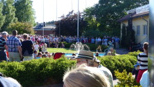 En bild på många människor som har samlats runt en liten staty. De står i en park med grönt gräs och buskar.