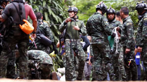 Räddningsarbetare omringad med utrustning jobbar för att få ut de instängda pojkarna från Tham Luang-grottan.