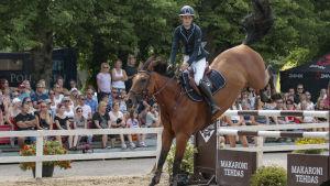 Häst landar på frambenen efter att ha hoppat över högt hinder.