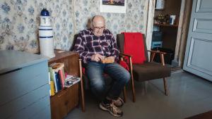 Vanhempi mieshenkilö istuu olohuoneen nojatuolissa sooloshakkia pelaten.