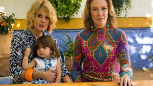 Kolmen sukupolven naiset istuvat pöydän äärellä ja katsovat jonnekin, samaan suuntaan. Lasta lukuun ottamatta.